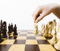 Hand hebt Figur auf Schachbrett